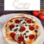 A pizza on a round wooden board with a jar of pizza sauce and fresh tomatoes in the background with text overlay reading crispy pizza crust.