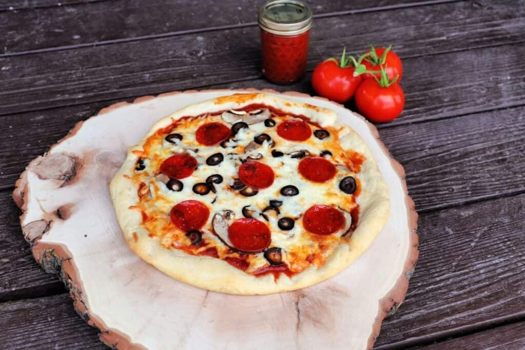 A pizza on a round wooden board with a jar of pizza sauce and fresh tomatoes in the background.