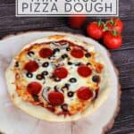 A pizza on a round wooden board with a jar of pizza sauce and fresh tomatoes in the background with text overlay reading crispy pizza crust with text overlay reading: easy, homemade thin crust pizza dough.