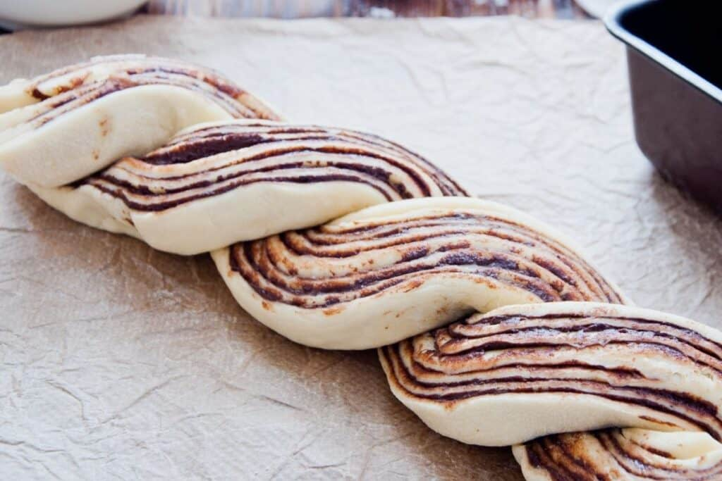 Bread dough halves exposing layers of jam twisted into 1 raw loaf.
