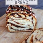 A loaf of jam filled bread sliced open exposing the bread and jam ribbons inside sitting on a wooden cutting board with text overlay stating: easy, homemade jam swirled bread..