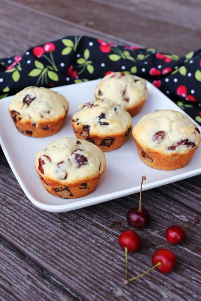 5 sour cherry chocolate chunk muffins on a square white plate as seen from above with fresh cherries in front and a black cloth covered in a red cherry pattern behind.