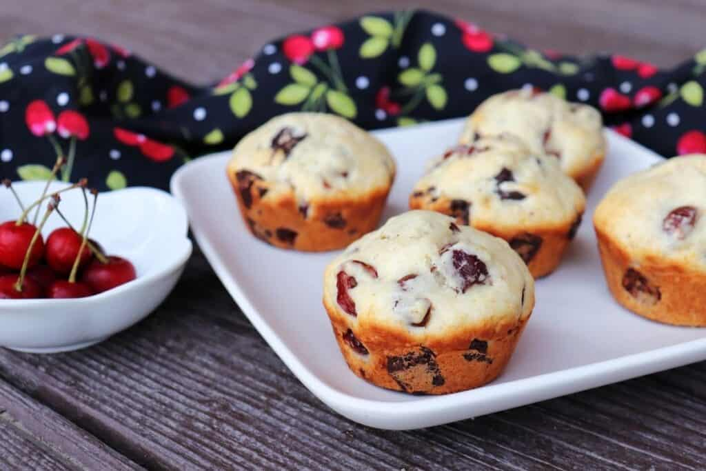 Sour cherry chocolate chunk muffins on a white plate with a bowl of fresh cherries sitting to the right.