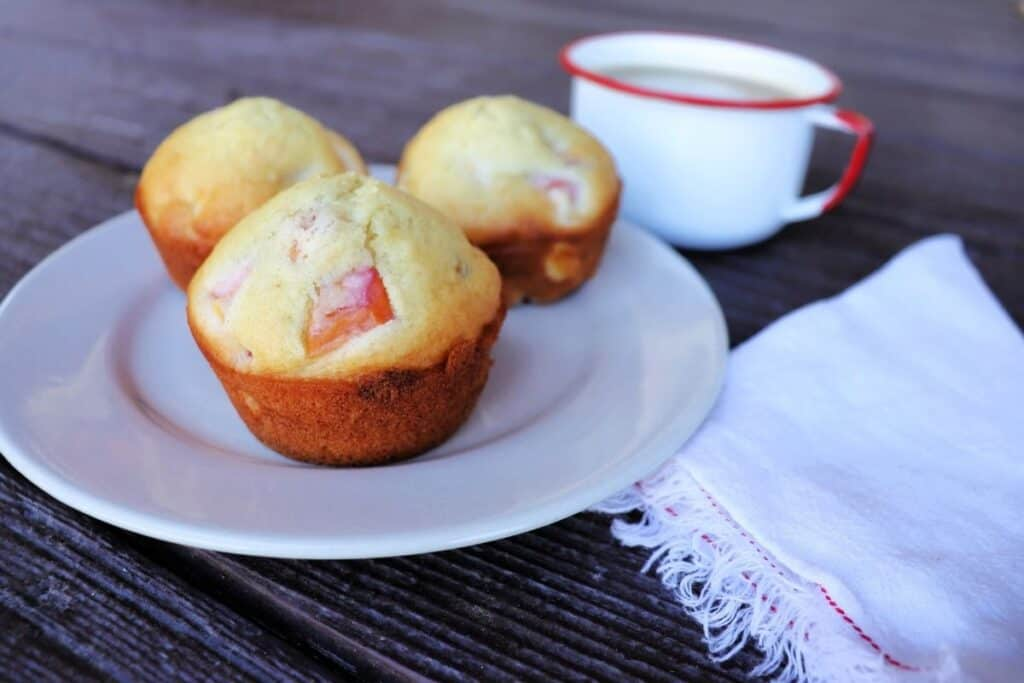 3 nectarine muffins on a plate with a white napkin sitting to the right and a cup of coffee in the background.