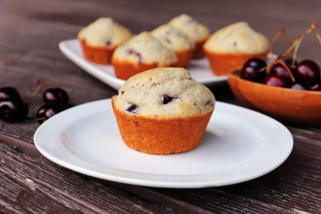 A muffins sitting on a white plate with a platter of more muffins in the background and a wooden bowl full of sweet cherries beside it.