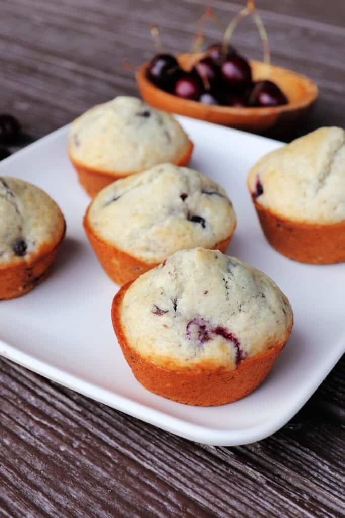 A square white plate with five muffins sitting on it, a wooden bowl of fresh cherries in the background.