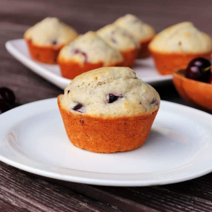 A cherry muffin on a white plate with platter of more muffins in the background.